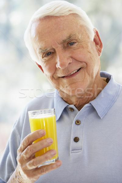 Foto stock: Homem · sorridente · câmera · potável · suco · de · laranja · feliz