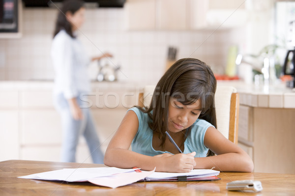 Young girl in kitchen doing homework with woman in background Stock photo © monkey_business