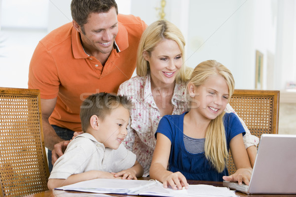 Couple helping two young children with laptop do homework in din Stock photo © monkey_business