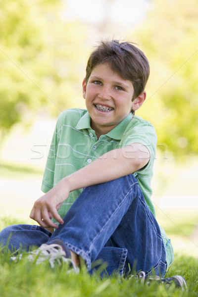 Young boy sitting outdoors smiling Stock photo © monkey_business