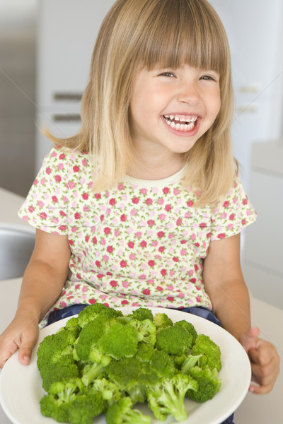 Young girl in kitchen eating broccoli smiling Stock photo © monkey_business