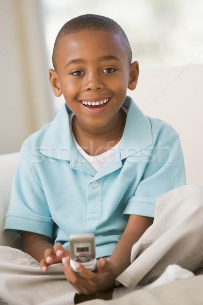 Młody chłopak posiedzenia sofa sms dziecko domu Zdjęcia stock © monkey_business