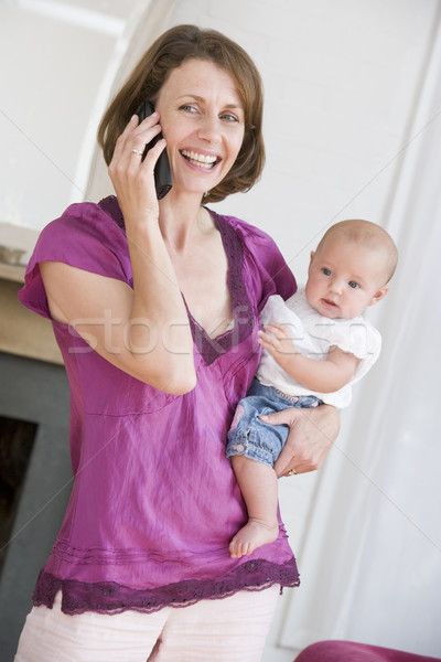 Mother in living room using telephone holding baby smiling Stock photo © monkey_business