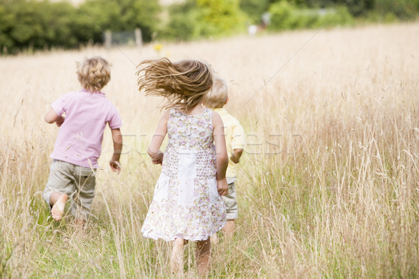 Stock photo: Three young children running outdoors