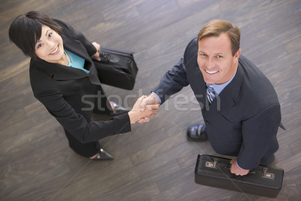 Two businesspeople indoors shaking hands smiling Stock photo © monkey_business