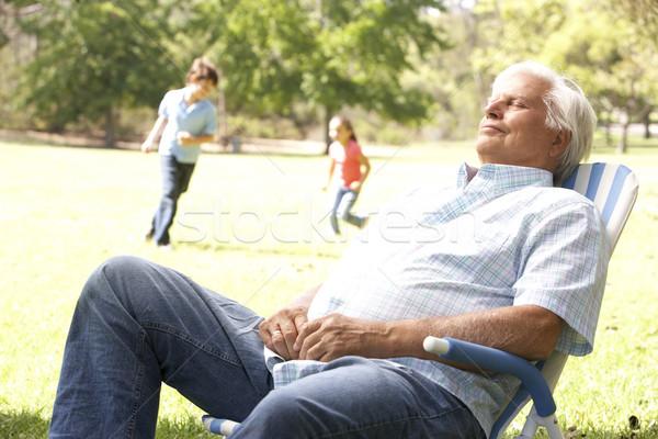 Stock photo: Senior Man Relaxing In Park With Grandchildren In Background