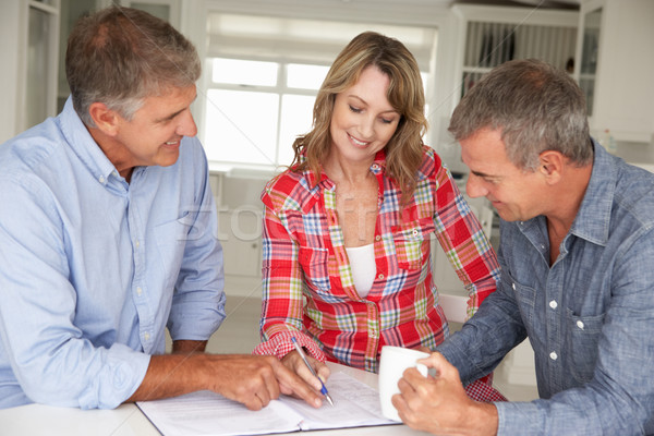Mid age couple with financial advisor at home Stock photo © monkey_business