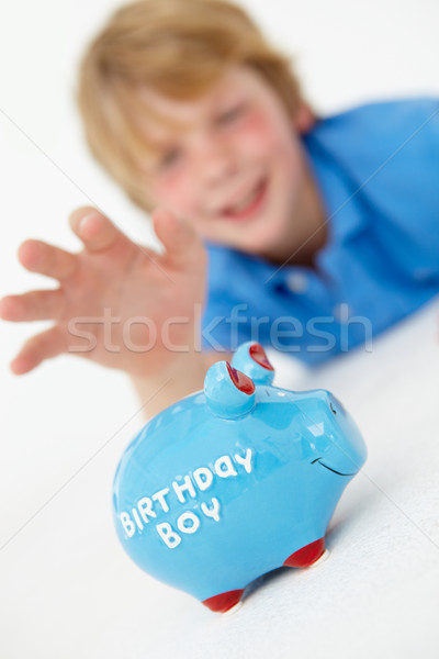 Young boy reaching for piggy bank Stock photo © monkey_business