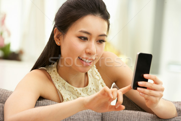 Young Chinese Woman Using Mobile Phone On Sofa At Home Stock photo © monkey_business