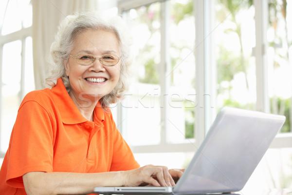 Senior chinesisch Frau Sitzung Schreibtisch mit Laptop Stock foto © monkey_business