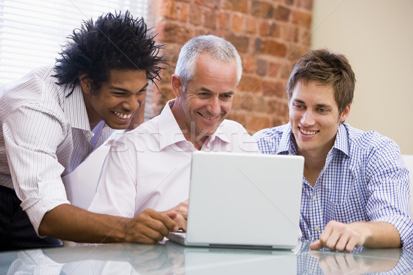 Three businessmen sitting in office with laptop smiling Stock photo © monkey_business