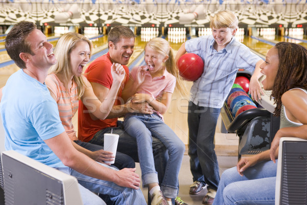 Family in bowling alley with two friends cheering and smiling Stock photo © monkey_business