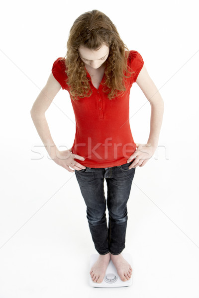 Unhappy Young Girl Standing On Scales Stock photo © monkey_business