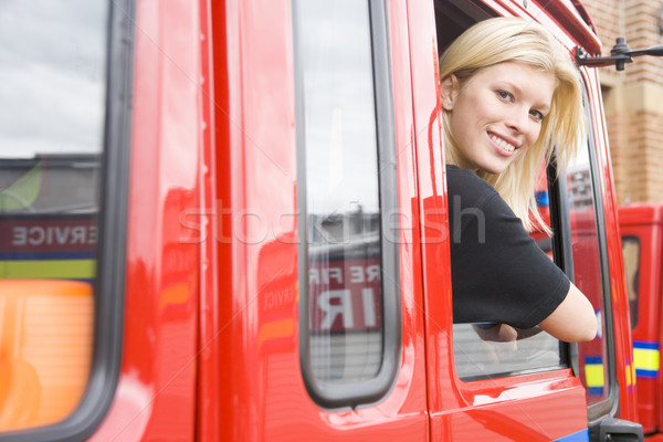 Female firefighter sitting in the cab of a fire engine Stock photo © monkey_business