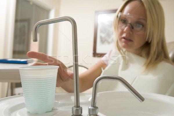 Woman in dental exam room reaching for water Stock photo © monkey_business
