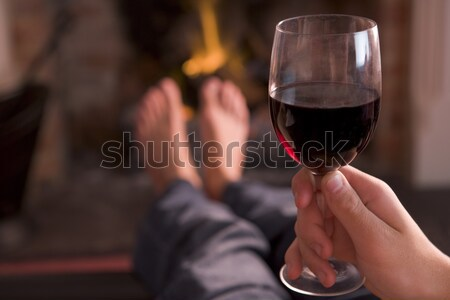 Feet warming at fireplace with hand holding wine Stock photo © monkey_business