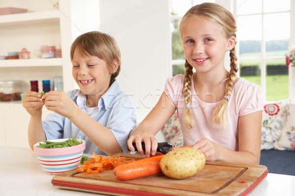 Happy children peeling vegetables in kitchen Stock photo © monkey_business