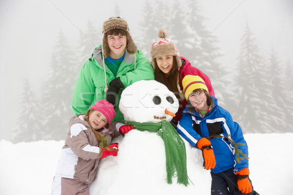 Group Of Children Building Snowman On Ski Holiday In Mountains Stock photo © monkey_business