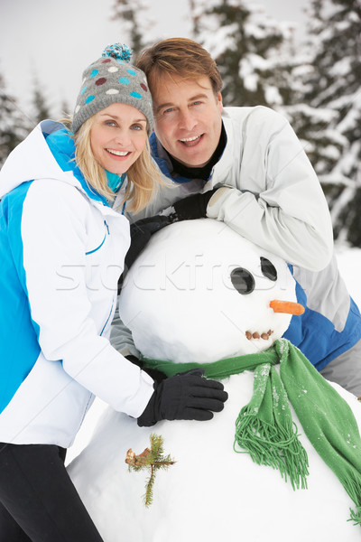 Middle Aged Couple Building Snowman On Ski Holiday In Mountains Stock photo © monkey_business