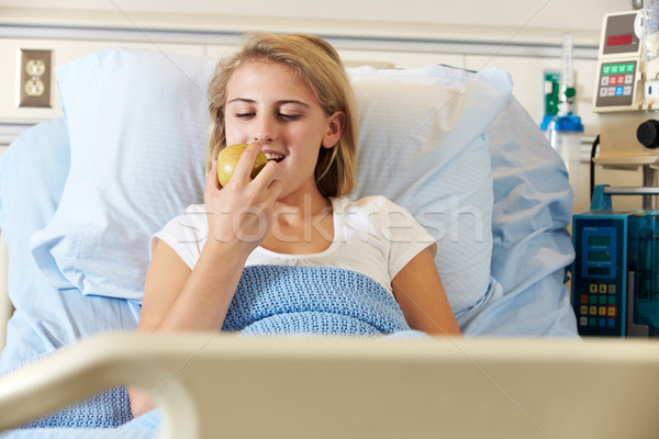 Adolescente feminino paciente alimentação maçã cama de hospital Foto stock © monkey_business