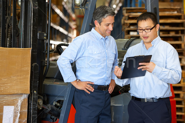 Businessmen Meeting By Fork Lift Truck In Warehouse Stock photo © monkey_business