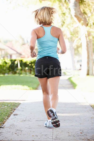Rear View Of Female Runner Exercising On Suburban Street Stock photo © monkey_business