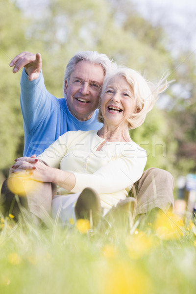 Couple relaxing outdoors pointing and smiling Stock photo © monkey_business