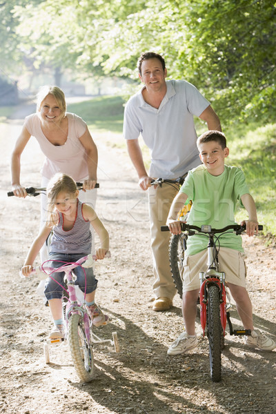 Stock photo: Family on bikes on path smiling