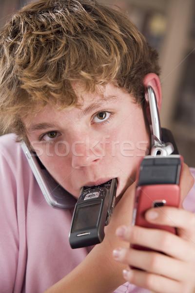 Młody chłopak sypialni wiele telefony komórkowe telefonu Zdjęcia stock © monkey_business