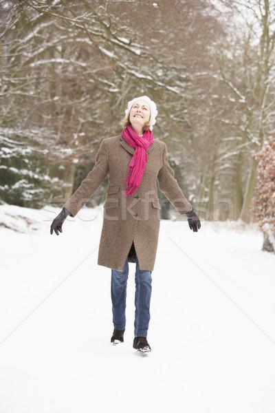 Senior Woman Walking Through Snowy Woodland Stock photo © monkey_business
