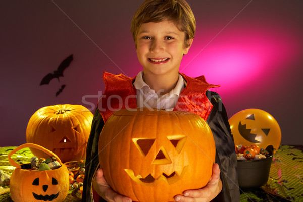 Halloween party with a boy child holding carved pumpkin Stock photo © monkey_business