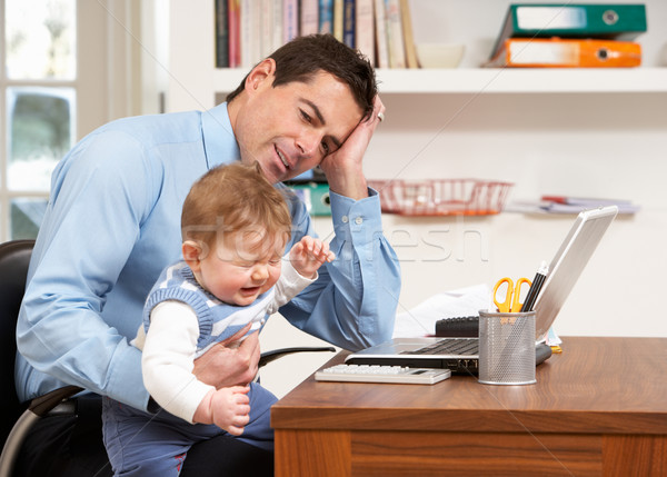 Stressed Man With Baby Working From Home Using Laptop Stock photo © monkey_business