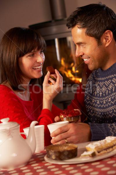Couple Enjoying Tea And Cake By Cosy Log Fire Stock photo © monkey_business