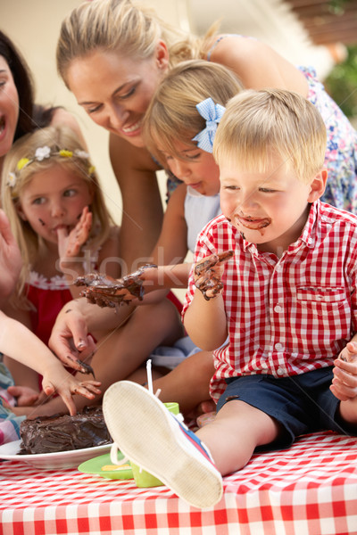 Children And Mothers Eating Cake At Outdoor Tea Party Stock photo © monkey_business