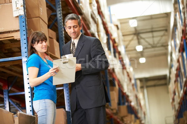 Stock photo: Businessman And Female Worker In Distribution Warehouse