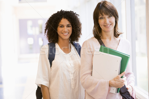 Two women with backpacks standing in a campus corridor Stock photo © monkey_business