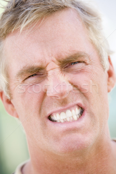 Stock photo: Head shot of man scowling