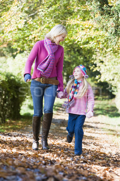 Mother and daughter walking along autumn path Stock photo © monkey_business
