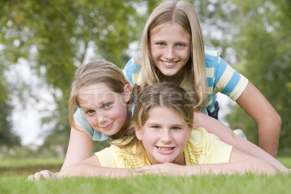 Three young girl friends piled on each other outdoors smiling Stock photo © monkey_business