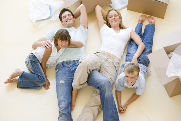 Family lying on floor by open boxes in new home smiling Stock photo © monkey_business