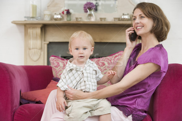 Stock photo: Mother using telephone in living room with baby smiling