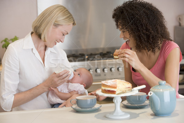 Mother and baby in kitchen with friend eating cake and smiling Stock photo © monkey_business