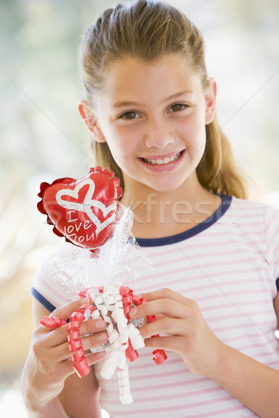 Stock photo: Young girl on Valentine's Day holding love themed balloon smilin