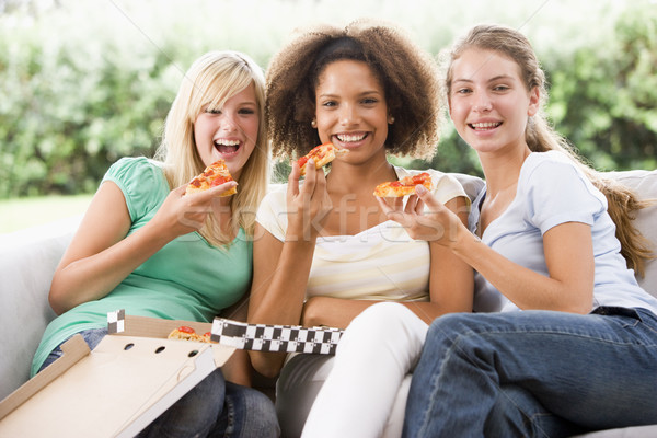 Tienermeisjes vergadering bank eten pizza samen Stockfoto © monkey_business