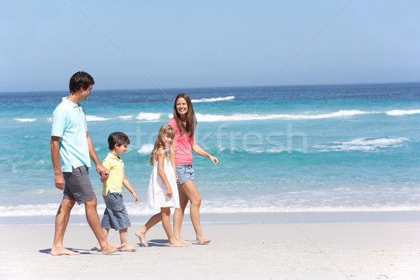 Family Walking Along Sandy Beach Stock photo © monkey_business
