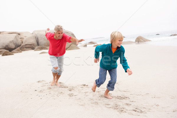 Grandfather Chasing Grandson Along Winter Beach Stock photo © monkey_business