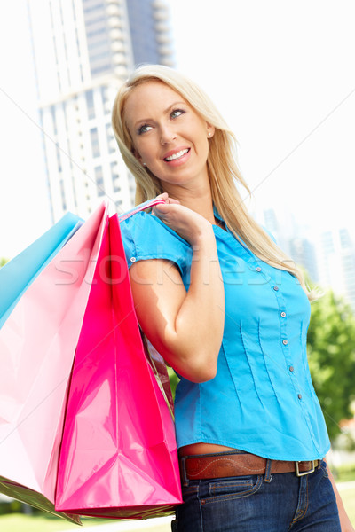 Woman carrying shopping bags in city park Stock photo © monkey_business