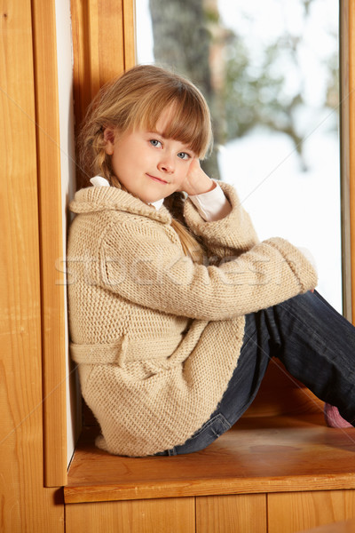 Young Girl Sitting On Window Ledge Looking At Snowy View Stock photo © monkey_business