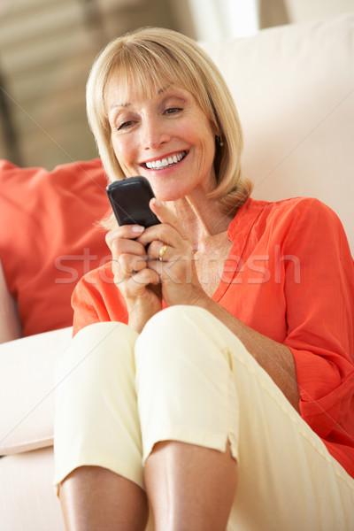Senior Woman Relaxing On Sofa Sending Text Message Stock photo © monkey_business