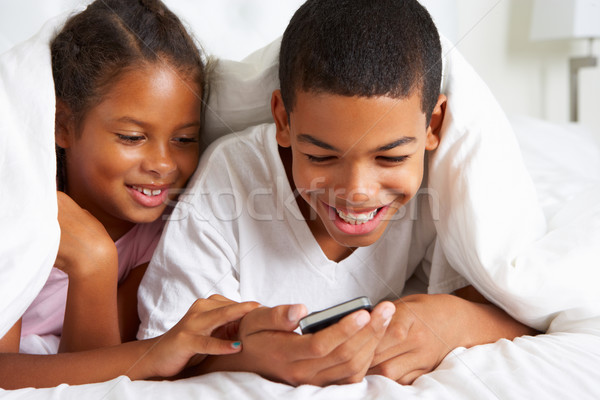 Two Children Using Mobile Phone Under Duvet Stock photo © monkey_business